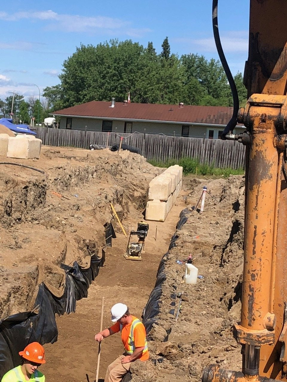 Workers digging and setting up a trench